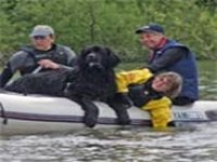 Picture of black Newfoundland dog with paws on edge of boat as smiling owner encourages it to leave